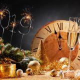 New Years Eve 2019 party background with flutes of champagne, decorations, and a clock counting down to midnight