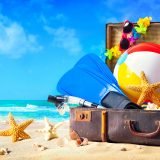 Preparation for summer vacation. Beach accessories in suitcase on sand. Family holidays concept