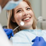 Image of pretty young woman sitting in dental chair at medical center while professional doctor fixing her teeth