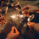 Happy New Year and Merry Christmas! Glasses with champagne in hand and sparklers.